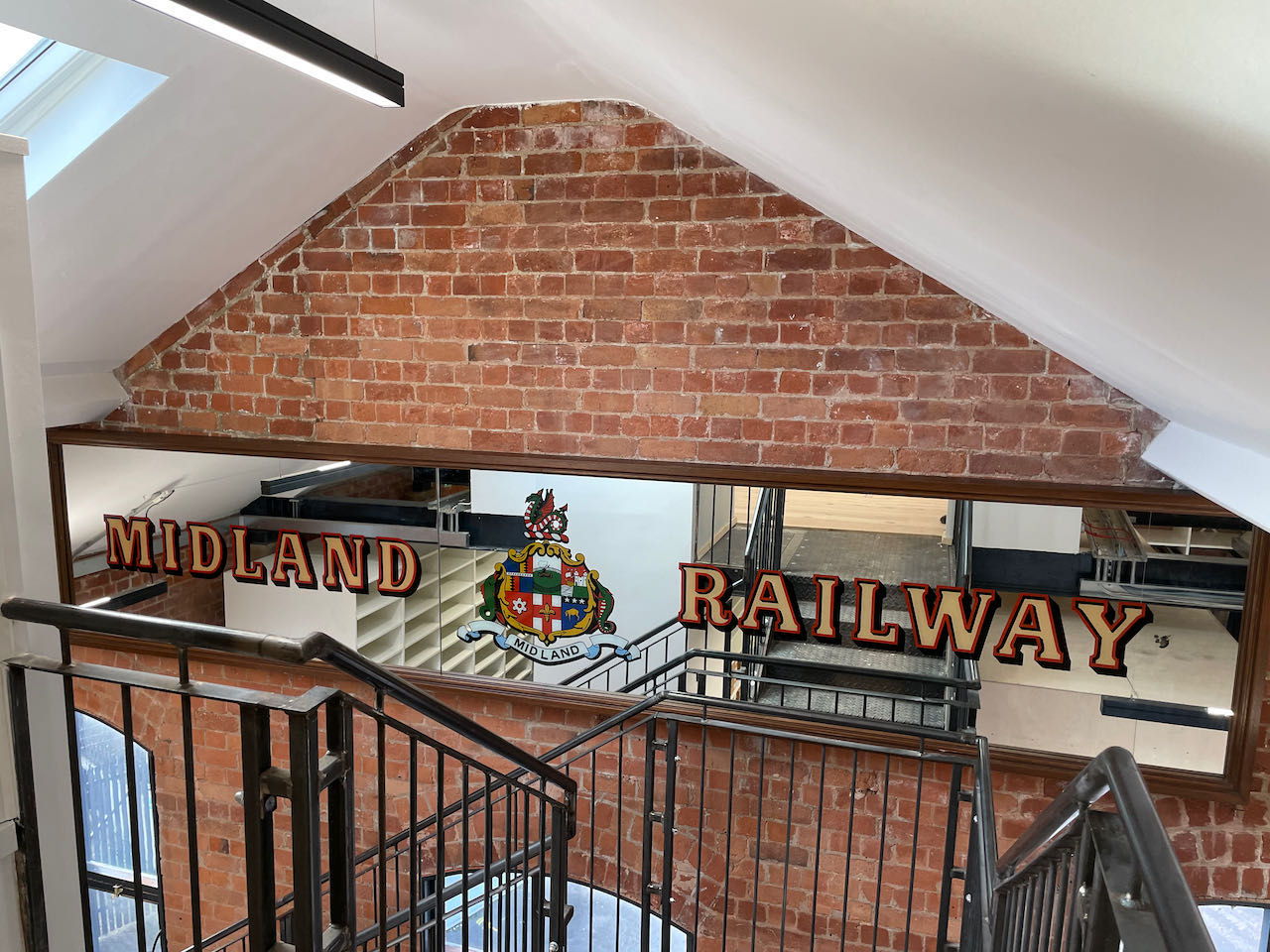 The Midland Railway Bradford bar mirror newly installed on the wall of the stairway separating the Midland Railway Study Centre reading room from the store below