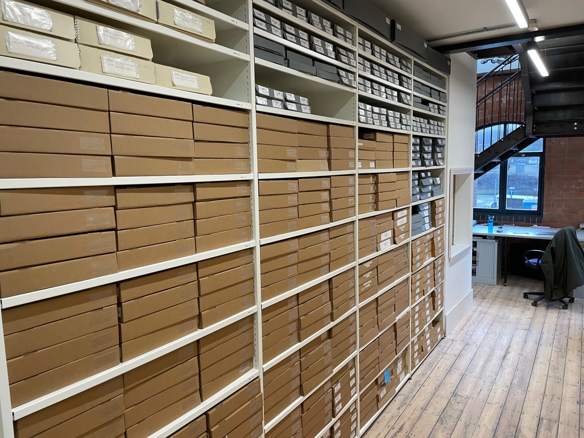Rows of light coloured steel shelves filled with tan boxes