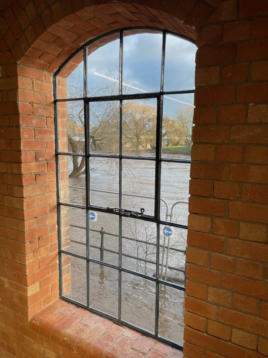 Viewed through an arched window, the River Derwent outside is in flood