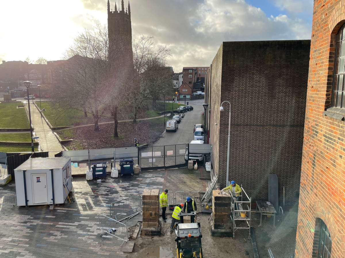 Viewed through a first floor window, workers are busy re-erecting two large stone pillars with Derby cathederal sillouetted by the low sun in the background