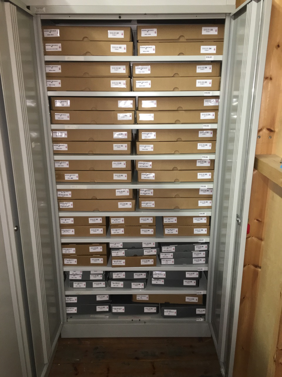 A steel cupboard filled from top to bottom with boxes containing archive material