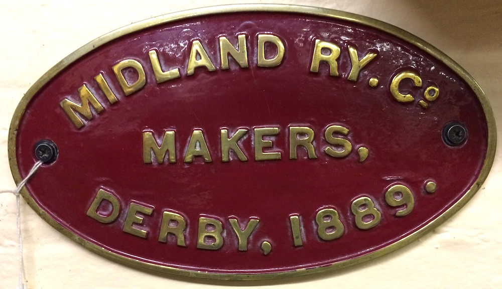 An oval cast brass plaque with maroon background which reads 'Midland Ry Co. -  Makers  -  Derby, 1889.'
